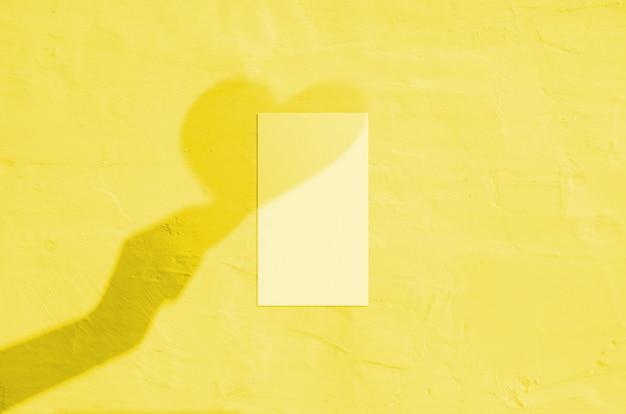 Cartão de visita vertical branco em branco sobre fundo coral com sombra de mão e coração