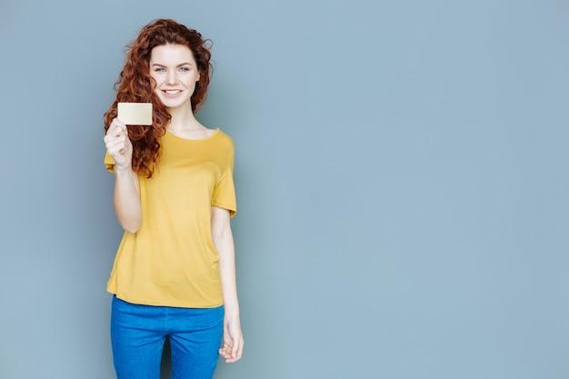 Cartão de visitas. mulher alegre e simpática olhando para você e sorrindo enquanto segura um cartão de visita