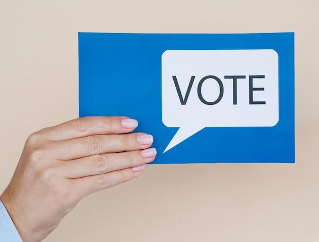 Cartão de vista frontal azul com bolha do discurso de votação com fundo bege