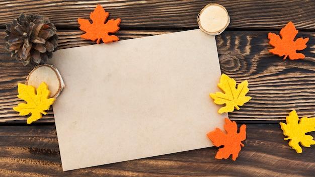 Cartão de vista superior com folhas no fundo de madeira