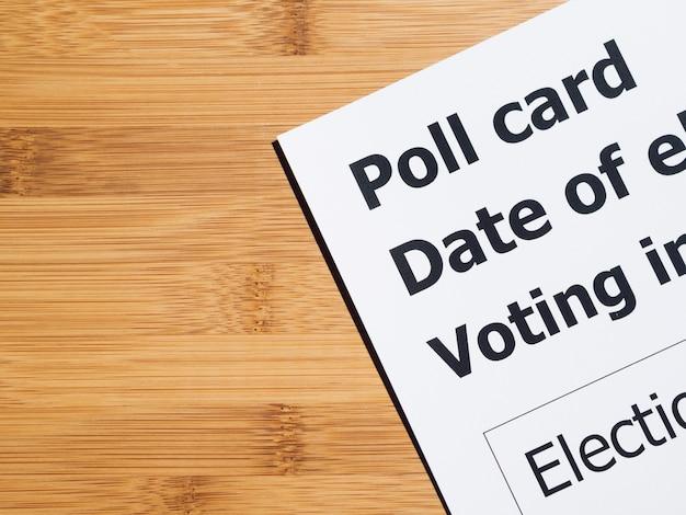 Cartão de votação no fundo de madeira
