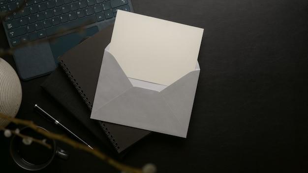 Cartão do convite aberto com envelope cinza acima livros de agenda preto com suprimentos e decoração