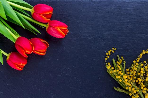 Cartão do dia das mulheres com tulipas e mimosa no fundo de pedra preto da placa.