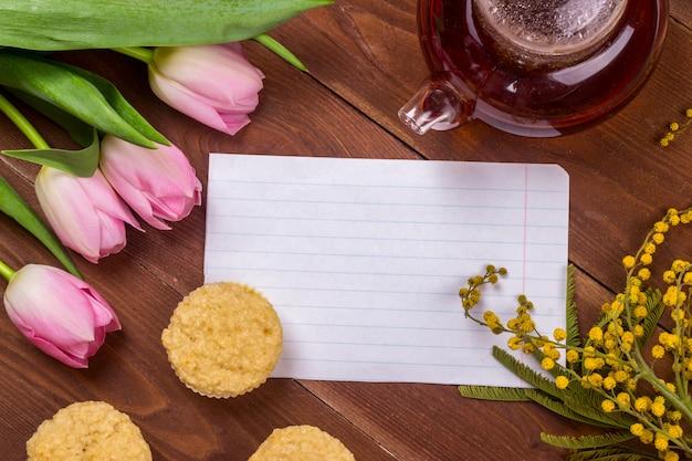 Cartão do dia das mulheres com tulipas, mimosa, chá e cupcakes no fundo de madeira marrom.