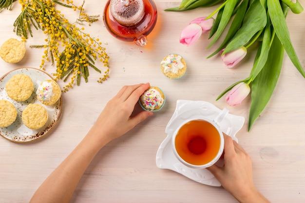 Cartão do dia das mulheres com tulipas, mimosa, chá e cupcakes no fundo de madeira.