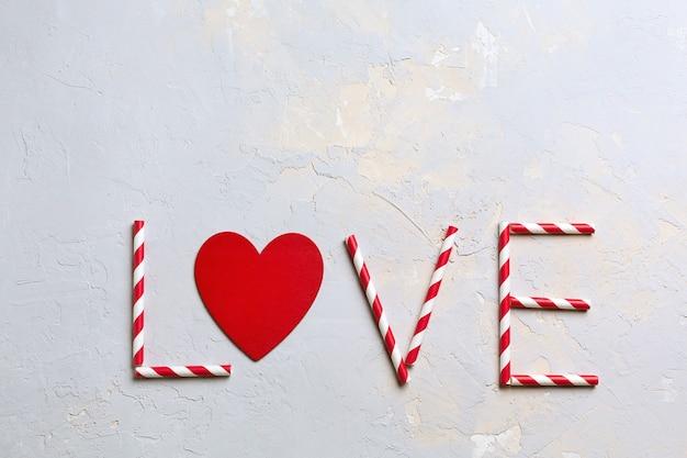 Cartão do dia de são valentim, palavra amor feito de canudos listrados e coração vermelho em textura cinza