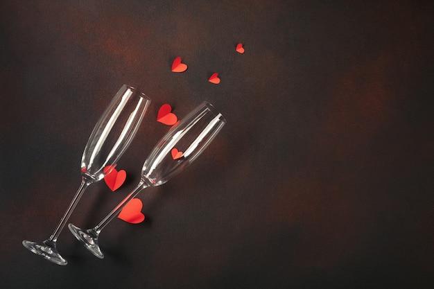 Cartão do dia de valentim com vidros do champanhe e corações dos doces no fundo de pedra.