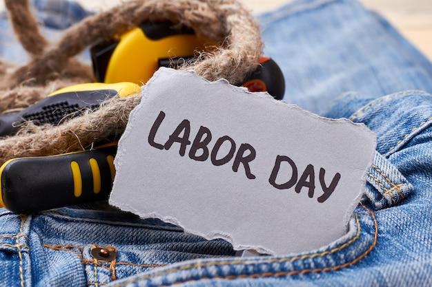 Cartão do dia do trabalho perto da corda. ferramentas e papel em jeans. relaxe nas férias.