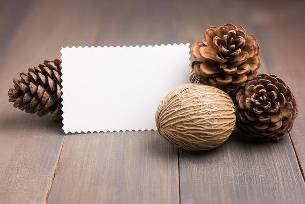 Cartão do livro branco, cones do pinho e semente do othalanga no assoalho de madeira marrom. Foto Premium