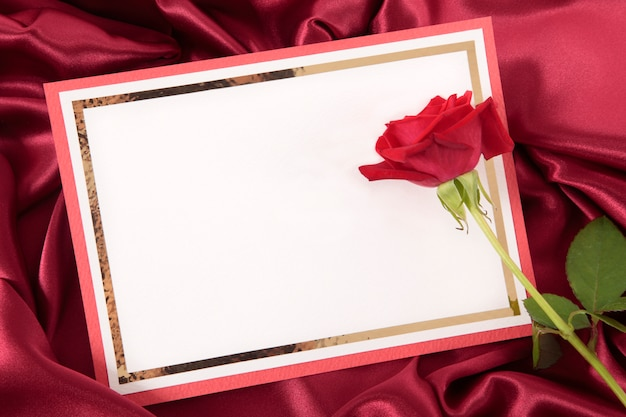 Cartão do valentim com levantou-se no fundo vermelho do cetim