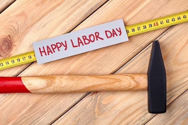 Cartão e martelo do dia do trabalho. ferramentas e cartão em madeira. simbolismo do dia do trabalho.