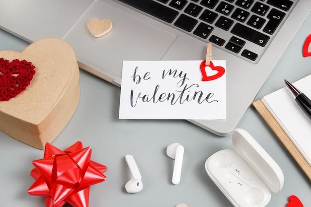 Cartão e presente de dia dos namorados seja meu valentim perto de aparelhos modernos na mesa cinza close-up. conceito de dia dos namorados