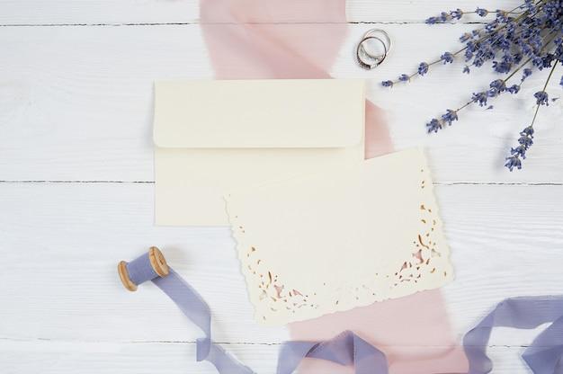 Cartão em branco branco, envelope e fita com dois anéis de casamento em tecido rosa