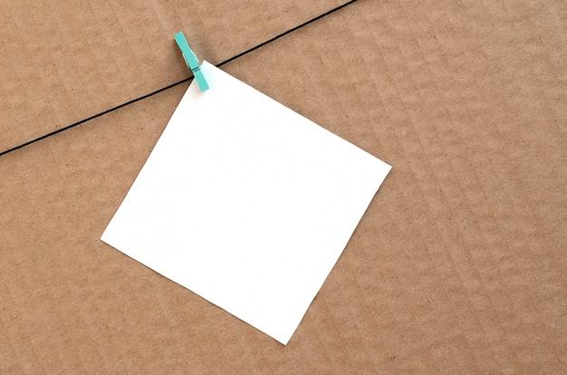 Cartão em branco branco na corda em um fundo de papelão marrom