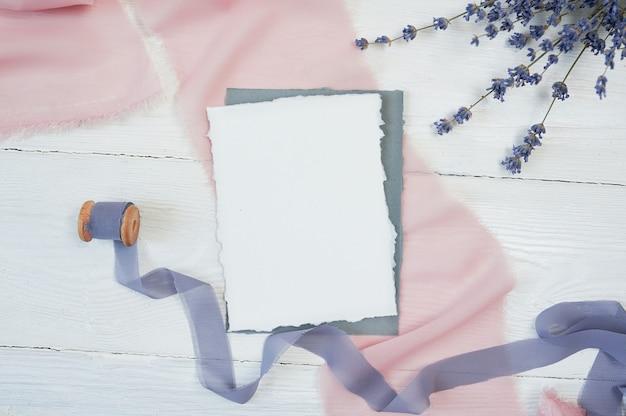 Cartão em branco branco sobre um fundo de tecido rosa e azul com flores de lavanda