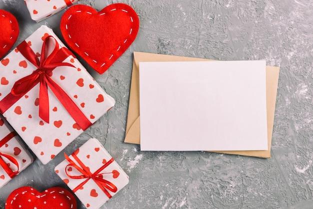 Cartão em branco, caixa de presente com corações, papel de embrulho e corações de têxteis