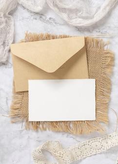 Cartão em branco com envelope deitado sobre uma mesa de mármore. cena de mock-up com cartão de papel de casamento. cama plana feminina elegante