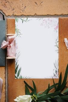 Cartão em branco com ornamentos florais repousa sobre um ladrilho de pedra marrom ao lado de um novelo de fitas verdes