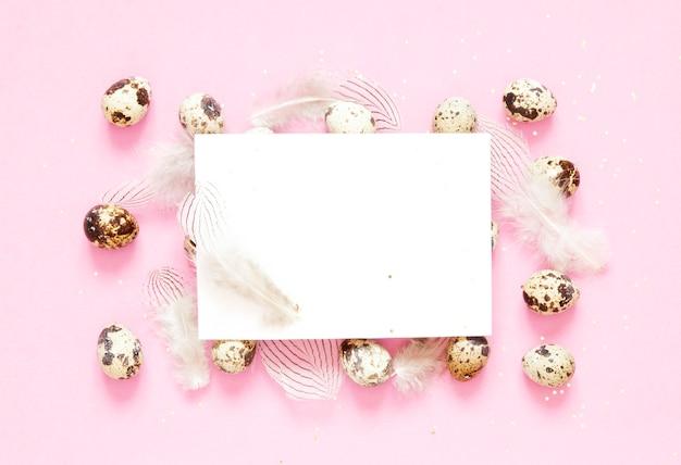 Cartão em branco. composição da páscoa com ovos da páscoa e plumagem no fundo cor-de-rosa.
