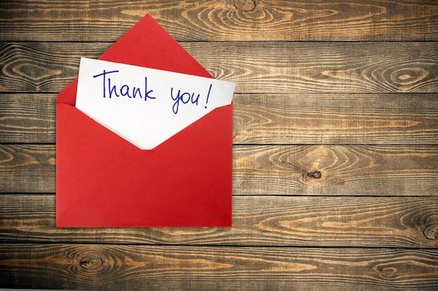 Cartão em branco e envelope com agradecimento no fundo