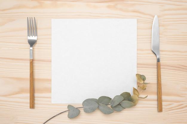 Cartão em branco e talheres na mesa de madeira rústica. faca e garfo com papel branco