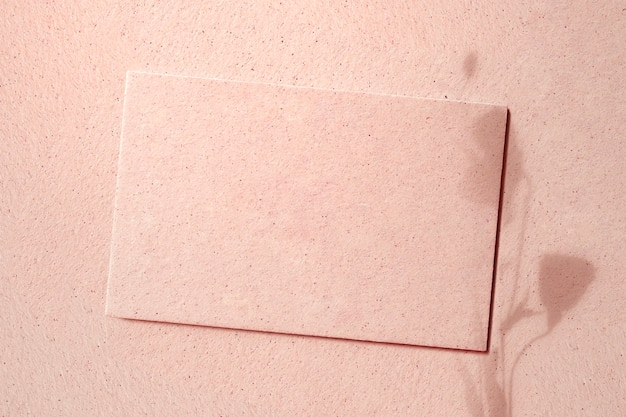 Cartão em branco em um concreto rosa