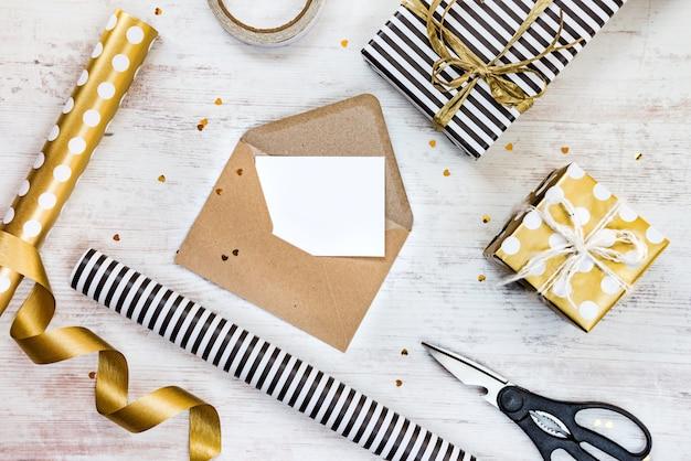 Cartão em branco em um envelope de ofício, caixas de presente e materiais de embrulho em um fundo branco de madeira.