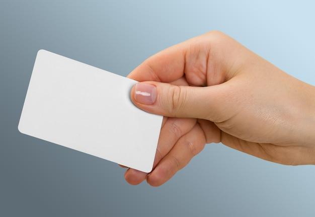 Cartão em branco na mão no fundo
