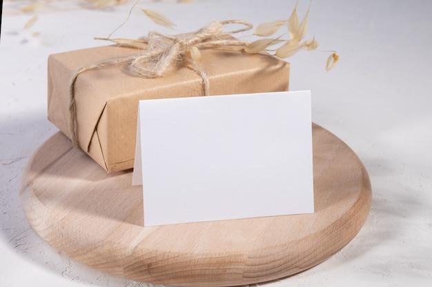 Cartão em branco ou nota com plantas secas, flor e caixa de presente