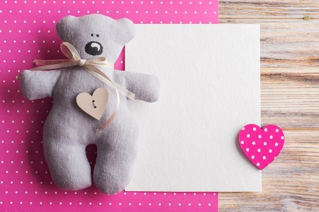 Cartão em branco sobre fundo rosa com ursinho de pelúcia