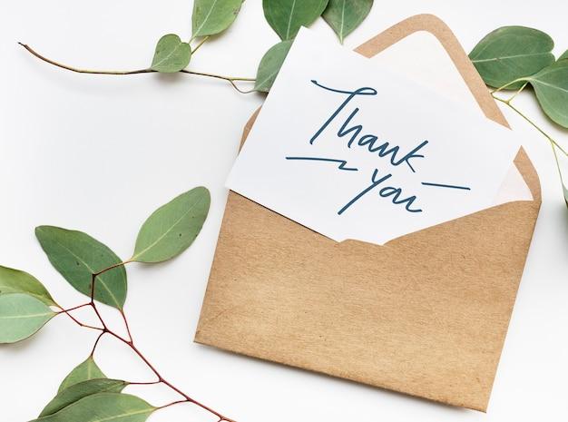 Cartão em uma maquete de envelope com folhas ao fundo