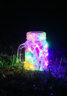 Cartão festivo com luzes coloridas guirlanda em frasco de vidro no fundo da natureza à noite.