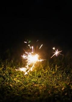 Cartão festivo com luzes de guirlanda coloridas brilhantes e fogo de bengali em frasco de vidro no fundo da natureza à noite.