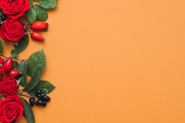 Cartão floral na época da colheita bagas vermelhas, folhas verdes e rosas em laranja