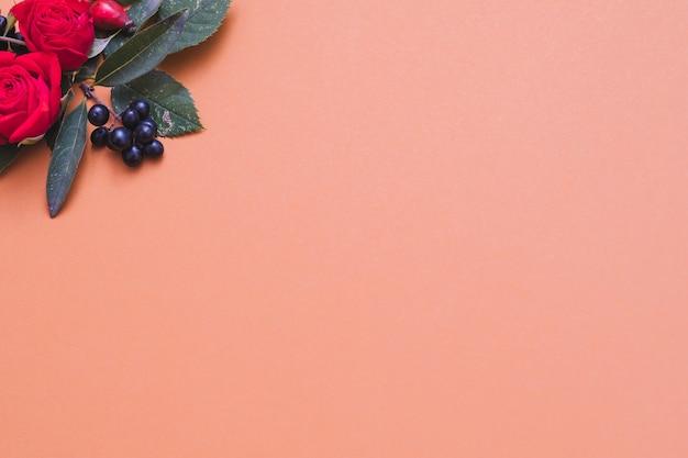 Cartão floral vermelho e preto caem bagas, folhas verdes e rosas em coral pastel