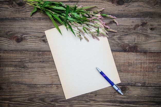Cartão: folha de papel, uma caneta e pequenas flores sobre fundo de madeira