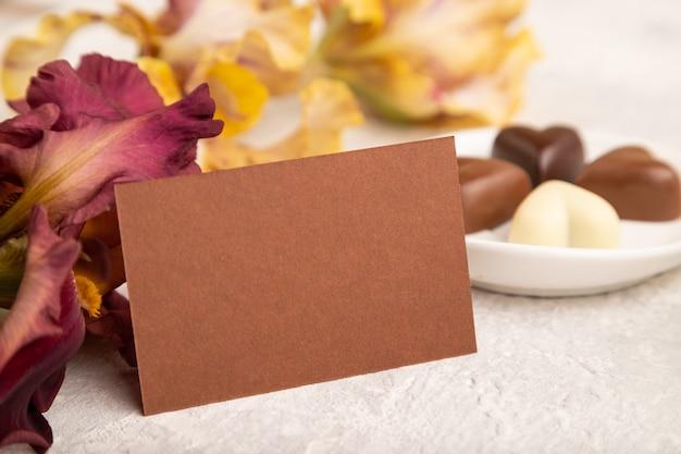 Cartão marrom com bombons de chocolate e flores de íris em fundo cinza de concreto. vista lateral