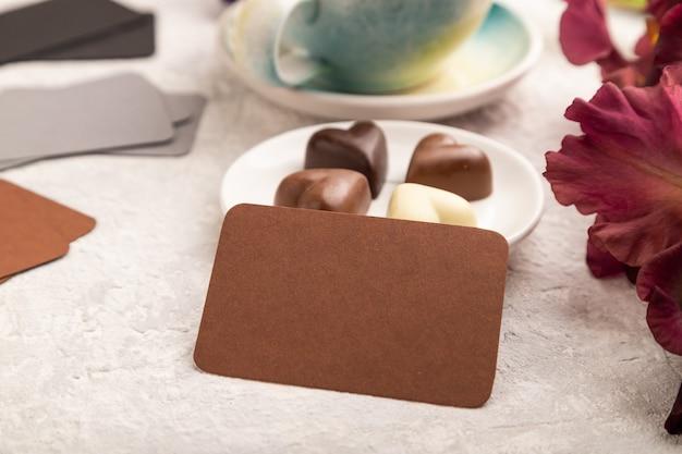 Cartão marrom com uma xícara de café, bombons de chocolate e flores de íris em fundo cinza.