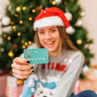 Cartão, mostrado, por, mulher, em, natal, chapéu