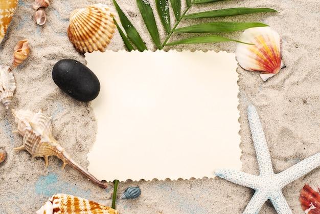 Cartão na areia ao lado de marisco