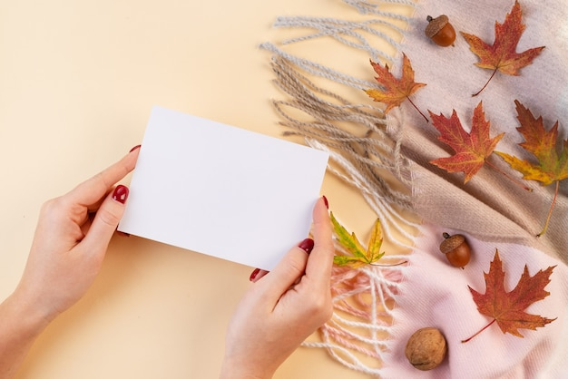 Cartão nas mãos em um fundo de outono - um lenço, nozes e folhas caídas em um fundo bege. vista do topo