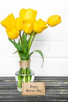 Cartão para dia das mães e tulipas amarelas na mesa de madeira