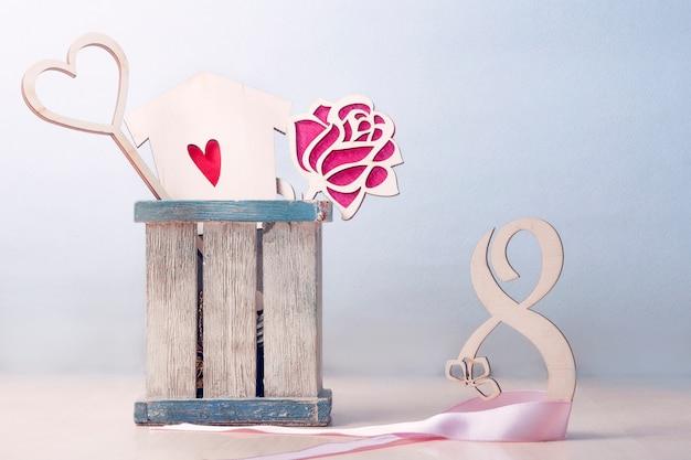 Cartão para o dia da mulher. à direita está o número 8 entrelaçado com uma fita rosa. caixa esquerda com um buquê de dois corações e rosas.