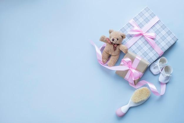 Cartão para o nascimento de uma menina com um urso de pelúcia presente e uma escova de cabelo de bebê na superfície cinza claro imagem com espaço de cópia