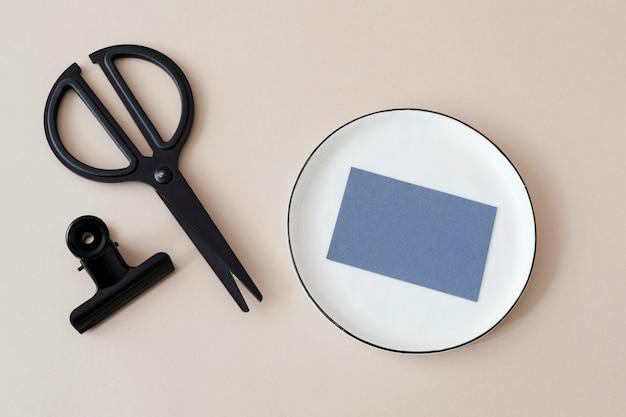 Cartão pessoal em branco e maquete de tesoura preta