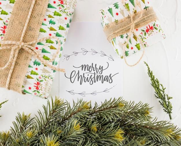 Cartão postal com a inscrição de natal feliz perto de presentes caixas e galhos de abeto
