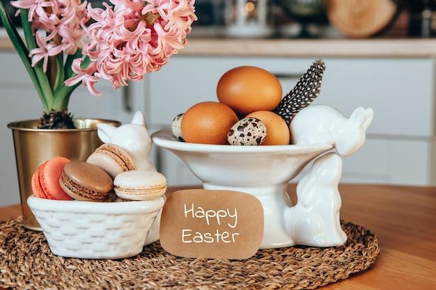 Cartão postal com a inscrição feliz páscoa ovos da páscoa macaroon bolos rosa jacinto e porcelana