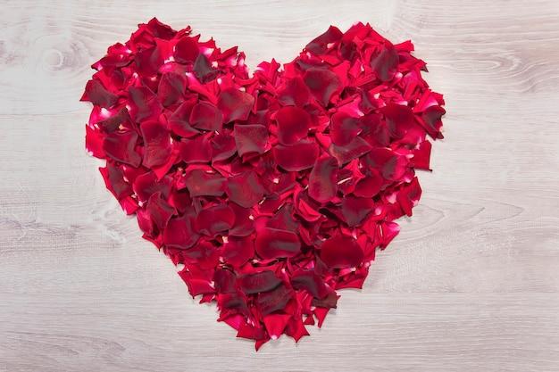 Cartão postal com um grande coração feito de pétalas de rosa vermelhas em uma mesa de madeira vintage branca