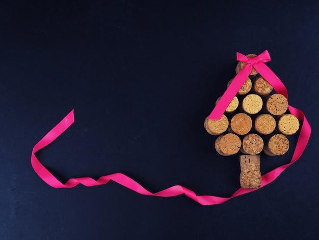Cartão-postal criativo para a nova árvore de natal-ano feita de cortiça e fita, sobre um fundo preto, espaço para texto