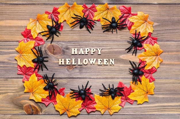 Cartão postal de halloween. madeira feita de folhas de bordo e aranhas